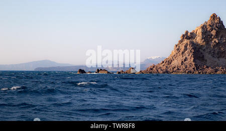 rocky shores off the coast of Santorini, Greece - Stock Photo