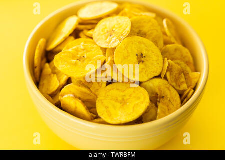 Baked Plantain Chips in Yellow bowl - a healthy snack - Stock Photo