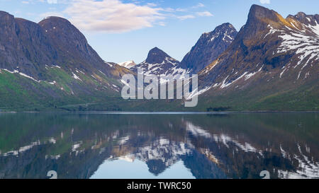 A beautiful mountain reflection is captured on the deep blue water of a fjord just off the National Scenic Route on the arctic island of Senja, Norway - Stock Photo
