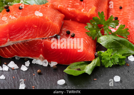 Fresh raw copper river sockeye salmon fillets on natural stone with herbs and seasoning - Stock Photo