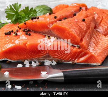 Fresh raw king salmon fillets on natural stone with herbs and seasoning - Stock Photo