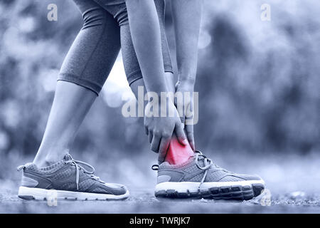 Broken twisted ankle - running sport injury. Female runner touching foot in pain due to sprained ankle. Stock Photo