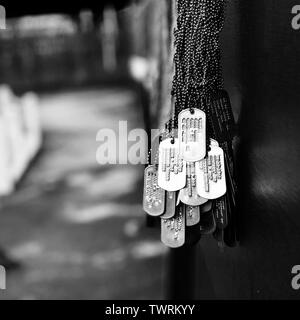 A collection of dog tags from fallen Vietnam war soldiers hanging from a wall