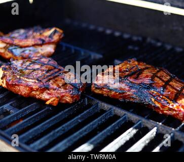 Three succulent pieces of t-bone steak on a gas grill with grill lines - Stock Photo