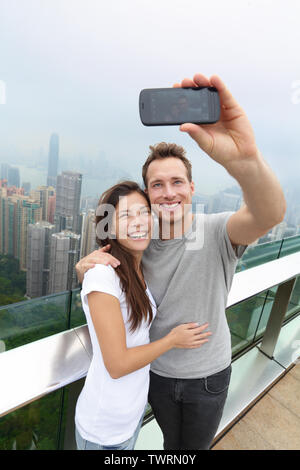 Hong Kong Victoria Peak tourists couple taking selfie photo picture with smartphone enjoying view over Hong Kong and Victoria Harbour. Young happy multiethnic couple traveling in Asia. - Stock Photo