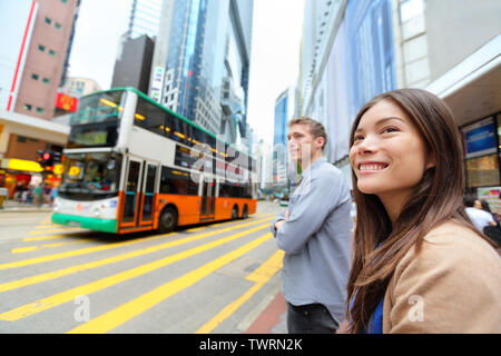 Hong Kong People walking in Causeway Bay crossing busy road with double decker bus. Urban mixed race Asian Chinese / Caucasian woman smiling happy living in city. - Stock Photo
