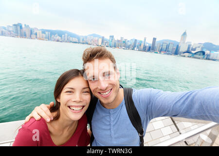 Selfie - Tourists couple taking selfportrait picture photo in Hong Kong enjoying sightseeing on Tsim Sha Tsui Promenade and Avenue of Stars in Victoria Harbour, Kowloon, Hong Kong. Travel concept. - Stock Photo