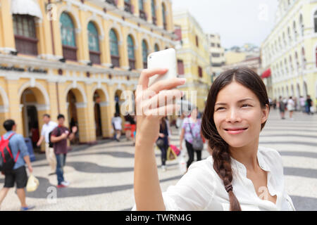 Woman tourist taking selfie pictures in Macau, China in Senado Square or Senate Square. Asian girl tourist using smart phone camera to take photo while traveling in Macau. Travel and tourism concept. Stock Photo
