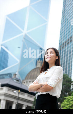 Asian business woman confident outdoor in Hong Kong standing proud in suit cross-armed in business district. Young mixed race female Chinese Asian / Caucasian female professional in central Hong Kong.