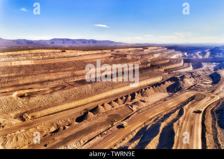Huge heavy trucks carrying raw minerals of black coal from the bottom of open cut coal mine in Upper Hunter Valley Liddell area, Australia. Elevated a - Stock Photo