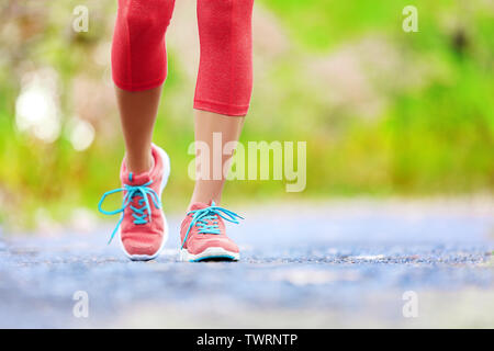Jogging woman with athletic legs and running shoes. Female walking on trail in forest in healthy lifestyle concept with close up on running shoes. Female athlete jogger training outdoors.