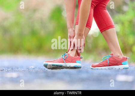 Twisted broken ankle - running sport injury. Female runner touching foot in pain due to sprained ankle. Stock Photo