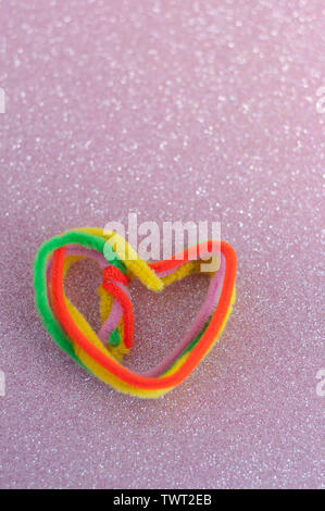 heart shaped using colourful crafts item. isolated on pink glitter background. Abstract design of crumpled. wallpaper with copy space. Love, passion, - Stock Photo