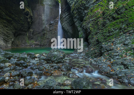 Kozjak waterfall in a cave surrounded by mossy rocks, with emerald pool and creek. Long exposure of famous tourist attraction Kozjak, Slovenia. - Stock Photo