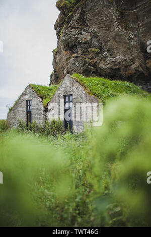 Two traditional iceland stone houses under rocky mountain with stone walls, roof covered with moss or grass. Green background. - Stock Photo