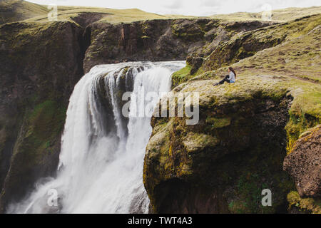 Woman sitting on edge with breathtaking view of Fagrifoss waterfall in Iceland. Lakagigar landmark in Skaftafell national park. - Stock Photo