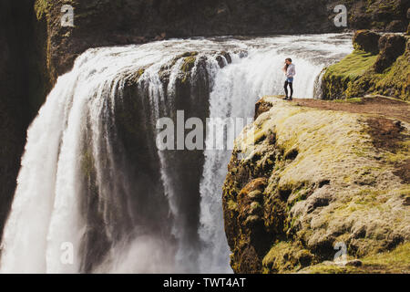 Woman standing on edge of cliff with breathtaking view of Fagrifoss cascade waterfall in Iceland. Wanderlust and travel concept. - Stock Photo