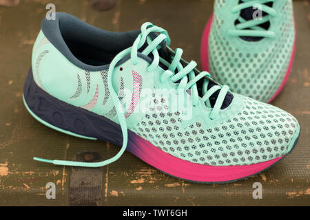 Pair of Perfect sneakers in pale blue for running. Green background. Shoes for longer races - Stock Photo