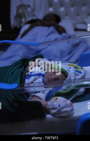 newborn mixed race baby boy sleeps, Cambodian mother sleeping in background, at a maternity hospital, Phnom Penh, Cambodia. credit: Kraig Lieb - Stock Photo