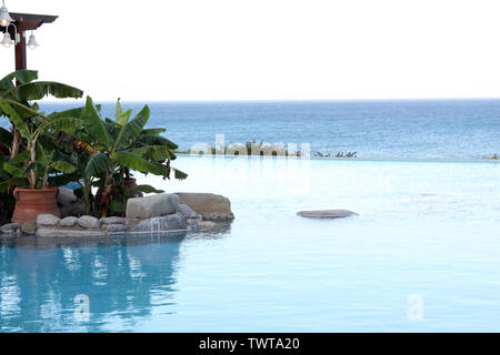 Rhodes, Greece - A view across hotel infinity pool with the sea in the background with blue white colour scheme, afternoon - Stock Photo