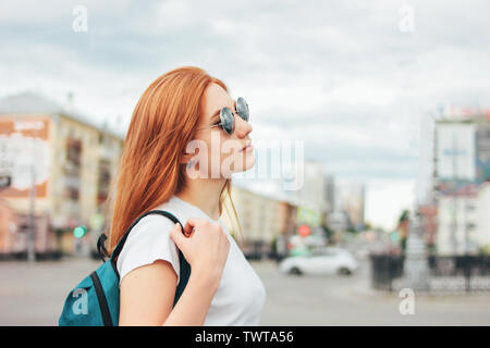 Attractive redhead smiling girl in sunglasses in casual clothes with backpack on street in the city - Stock Photo