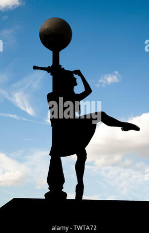 London, England, UK - Silhouette of a ballerina leaning against a lamppost along the river Thames against a blue sky background - Stock Photo