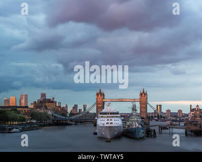 London, England. June 21, 2019. Cloudy sky over Tower Bridge as Silver Wind cruise ship moors next to HMS Belfast on the River Thames in London - Stock Photo