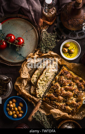 Sliced homemade focaccia bread and knife with olive oil and olives on rustic table , top view. Italian food concept.