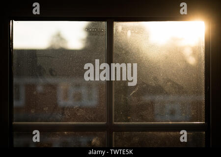 Sun rising over rooftop, seen through house window misted by dust and condensation; landscape format. - Stock Photo