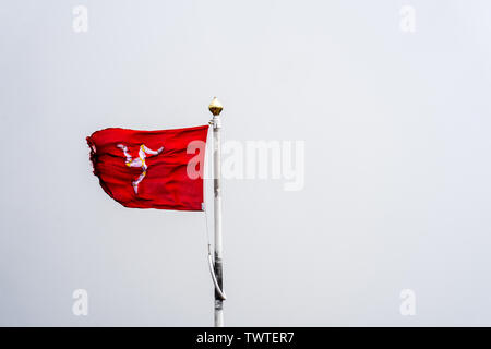 The flag of the Isle of Man or flag of Mann is a triskelion, composed of three armoured legs with golden spurs, upon a red background - Stock Photo