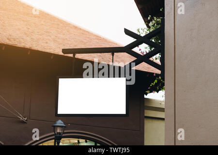 Empty signage and blank mock up hanging on street with copy space - Stock Photo