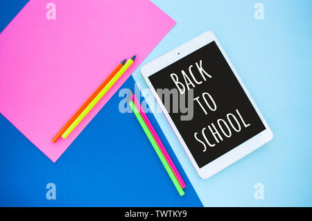 Colorful paper, neon pencils and tablet on blue and pink background with text space. Back to school concept. - Stock Photo