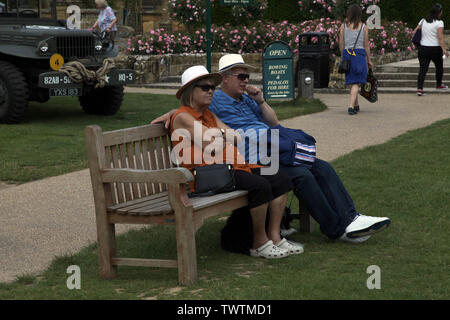 Edenbridge, Kent, UK - Older couple sitting outside on a bench watching the world go by in daytime on a sunny day - Stock Photo