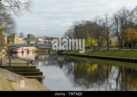 Quiet scenic riverside setting by Lendal Bridge (trees reflected in River Ouse & woman reading on riverbank) - York, North Yorkshire, England, UK. - Stock Photo