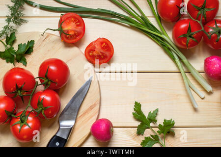 Healthy food cooking concept. Fresh tomatoes on branch, radish, onion, dill and parsley laid out on rustic light wooden table. Knife on kitchen board.