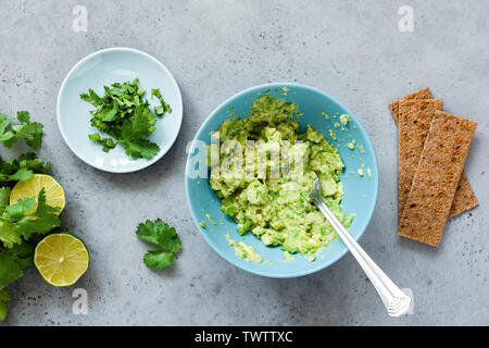 Mashed avocado in bowl and rye crispbreads. Making guacamole sauce, healthy vegetarian appetizer or snack. Top view - Stock Photo
