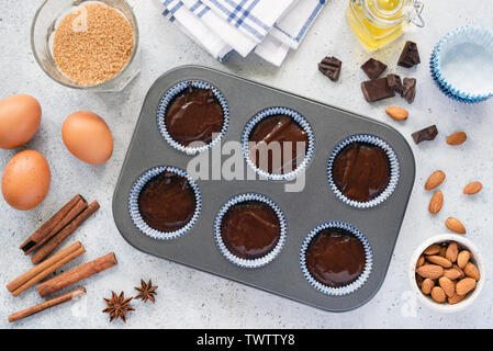 Homemade cupcakes or muffins dough in baking tin. Preparation of sweet chocolate pastry. Baking ingredients and utensils background, top view - Stock Photo