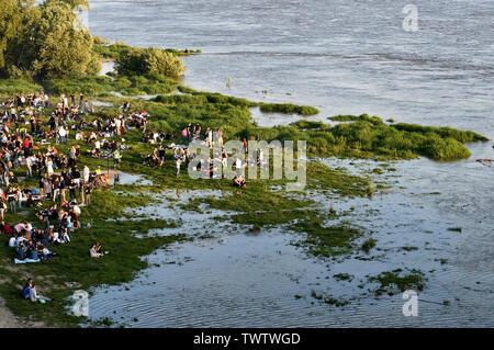 People resting on flooded riverbank, Vistula River, Warsaw, Poland - Stock Photo