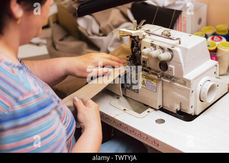 an elderly woman sews on a sewing machine. tailor embroiders in production. retired engaged favorite hobby. - Stock Photo