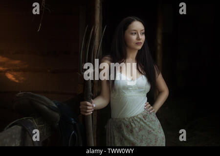 Young woman stands with a pitchfork near a stable on a ranch. - Stock Photo
