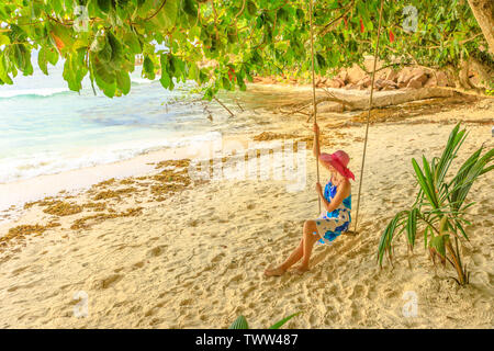 Elegant tourist woman with wide hat sitting on swing under tropical trees and looking at sea of Anse Severe in La Digue, Seychelles, Indian Ocean - Stock Photo