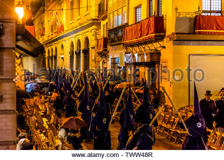 Hooded Penitents (Nazarenos) in the procession of the Brotherhood (Hermandad) El Baratillo, Holy Week (Semana Santa), Seville, Andalusia, Spain. - Stock Photo