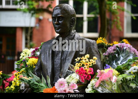 Alan Turing statue with flowers - Stock Photo