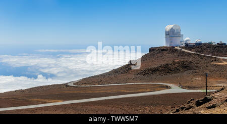 A curving road high above the clouds, with a radio telescope in sight. Haleakala Crater, Maui, Hawaii, USA - Stock Photo