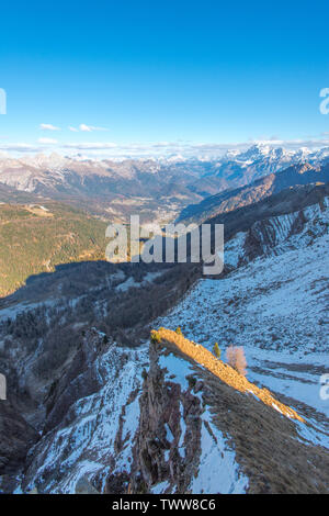 Mountain town in the Italian Dolomites, city of Falcade as seen from Forcella Venegiota. November hike in the mountains of Italy, fresh snow. - Stock Photo