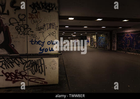 Croatia, Zagreb, June 21, the dark passage of a deserted, eerie creepy concrete indoor urban pathway grafted with graffiti at night - Stock Photo