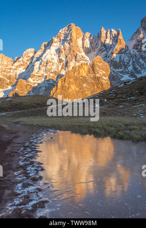 Golden mountains reflected on the water of a frozen lake in the Italian Dolomites. Mountain range during golden hour, water reflections of peaks. - Stock Photo