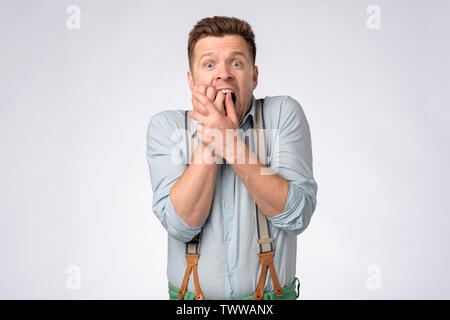 Young man in shirt and suspenders covering mouth with hands in shock - Stock Photo