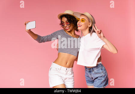 Two cheerful young diverse women taking selfie on smartphone - Stock Photo