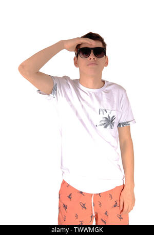 A tall young teenager boy in a white shirt and Bermuda shorts wearing sunglasses looking fare away, isolated for white background - Stock Photo